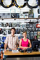 Storekeeper and assistant by counter in shop, smiling, portrait
