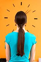 Woman looking at wall clock, rear view