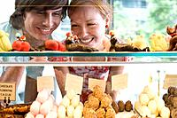 Couple looking at food on display in bakery, view through glass (thumbnail)