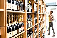 Woman looking at wine in shop (thumbnail)