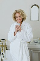 Woman with in bathroom with coffee