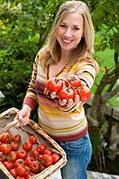 Woman with basket of tomatoes, smiling, portrait