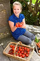 Girl 9-11 with basket of tomatoes, smiling, portrait