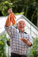 Senior man with carrots, smiling, portrait