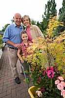 Senior couple and granddaughter 8-10 in garden centre, portrait