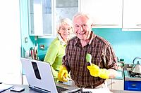 Senior couple in kitchen with laptop computer, portrait