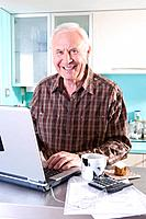 Senior man with laptop computer in kitchen, portrait