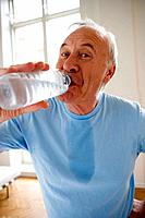 Senior man drinking from water bottle, portrait