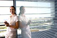 Businesswoman with electronic organiser by window in office, portrait