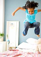 Mixed race girl jumping on bed (thumbnail)