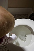 Child reaching into toilet