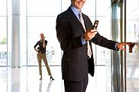 Businessman with mobile phone pressing elevator button, mid section