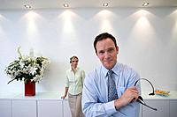 Businessman and woman with headsets in conversation, smiling