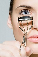 Woman with eyelash curler