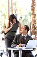 Businessman and businesswoman working in cafe