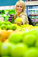 Woman choosing apples in grocery store