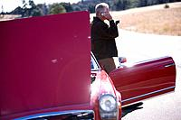 Man talking on cell phone next to broken down red convertible (thumbnail)
