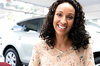 Woman smiling in car showroom (thumbnail)