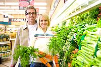 Couple choosing carrots in grocery store