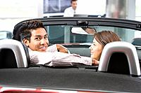 Couple sitting in convertible in car showroom