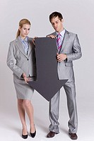 Businessman and businesswoman holding black arrow sign