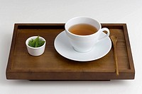 Black tea with spoon on tray and leaves in bowl, elevated view