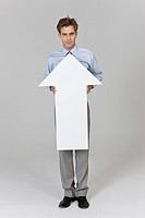 Businessman holding arrow sign, portrait