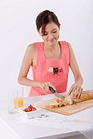 Young woman slicing loaf, close_up
