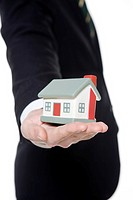 Businessman holding model house, close_up