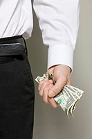 Midsection of businessman holding paper currency