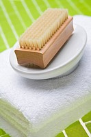Close_up of back brush in soap dish on folded towel