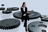Businesswoman sitting on machine gear wheel using laptop
