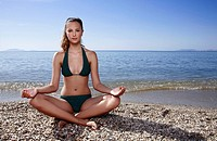 Female young adult doing yoga on beach (thumbnail)