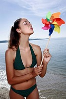 Female young adult blowing wind mobile on beach