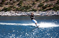 Young adult male waterskiing