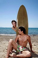 Young adult couple posing with surfboard