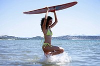 Female young adult with surfboard in water
