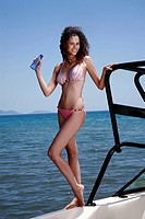 Female young adult on boat posing with water bottle