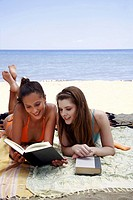 Two female young adults reading books on beach