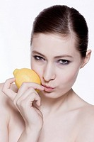Naked woman holding lemon, portrait