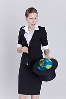 Businesswoman holding globe in hat, portrait