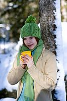 portrait of young woman in winter drinking hot tea