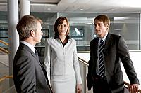 three business people having conversation in office building