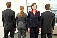 portrait of four business people standing in line one standing with face to camera