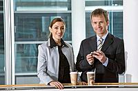 portrait of two executives having break one holding mobile phone