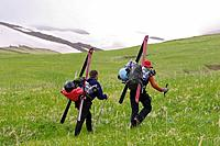 Two skiers hiking up a grassy slope on Umnak island in the Aleutian Islands