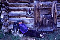 A Man Napping by a Log Cabin After Climbing Near Moab Utah