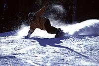 Snowboarding on a sunny day iin the Wasatch mountains in Utah