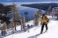 A man climbing on skis above Emerald Bay in Lake Tahoe California