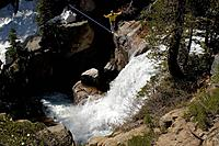 A man walking a tight rope above a waterfall near Tahoe City CA